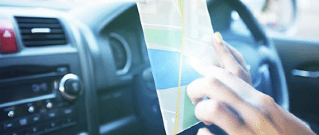 Inifrån bil, förerare som läser kartan på en iPad
