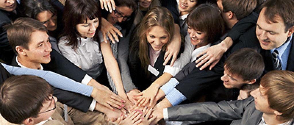 bild på ungdomar tagen uppifrån, alla står i en cirkel och har lagt händerna på varandra i mitten